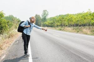 giovane donna hipster che fa l'autostop su una strada di campagna aspetta l'auto foto