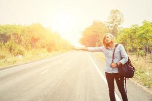 giovane donna hipster che fa l'autostop su una strada di campagna foto