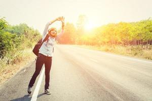 donna hipster che fa l'autostop su una strada di campagna alla ricerca dell'auto foto