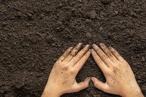 mano che tiene il terreno nero per coltivare il concetto di giornata mondiale del suolo delle colture foto