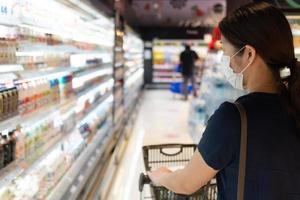 giovane donna che indossa una maschera per la spesa al supermercato? foto