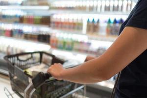 giovane donna che utilizza il carrello per acquistare generi alimentari nel supermercato foto