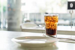 bicchiere di cola ghiacciata sul tavolo foto