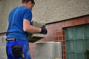 il muratore mette blocchi prefabbricati di cemento sul muro foto
