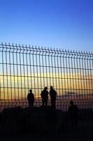 silhouette di persone dietro il recinto della grata foto