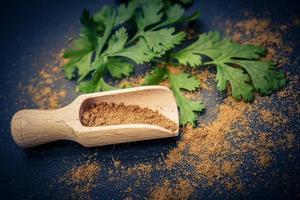 polvere di coriandolo marrone e cucchiaio di legno foto