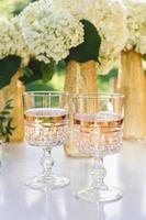 vino rosato in bicchieri. vino rosato su sfondo di bottiglie d'oro foto