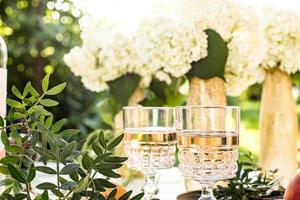 vino rosato in bicchieri su bottiglie dorate con fiori e frutti foto