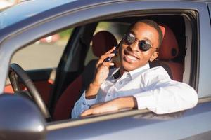 felice afroamericano alla guida di un'auto con un telefono, in estate foto