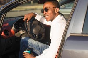 felice afroamericano alla guida di un'auto, in estate foto