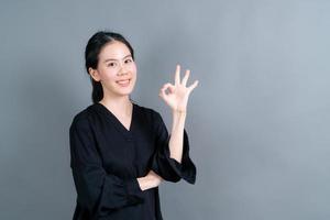 giovane donna asiatica che sorride e che mostra il segno giusto? foto