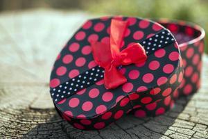 confezione regalo a forma di cuore su tronco di legno foto