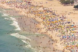 spiaggia di copacabana piena in una tipica domenica di sole a rio de janeiro. foto