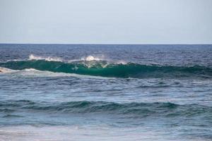 onda che si infrange sulla terza lastra della spiaggia di arpoador a rio de janeiro. foto