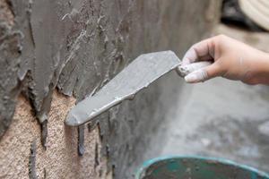 Donna con secchio versando cemento su un muro a rio de janeiro, brasile foto