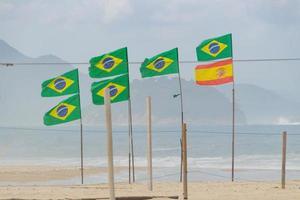 Molte bandiere del brasile e una della spagna all'aperto sulla spiaggia di copacabana a rio de janeiro, brasile foto