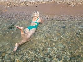 una ragazza bionda sdraiata a pancia in giù nell'acqua di mare trasparente foto