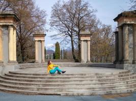 ragazza sorridente seduta sulle scale del parco guardando il sole primaverile foto