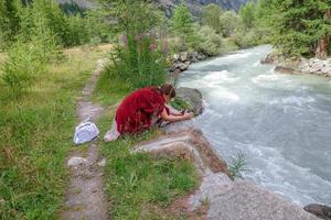 donna piegata sopra il fiume di montagna a fotografare il paesaggio foto