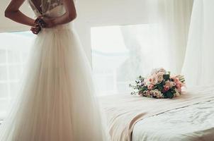 bouquet da sposa su un letto, sposa sfocata che si abbottona il vestito, vista posteriore foto