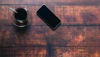 tazza di caffè, smartphone sulla scrivania foto