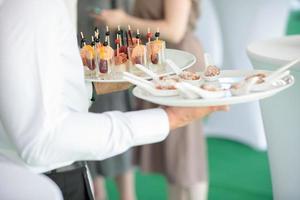 cameriere che porta piatti con stuzzichini in qualche evento festivo foto