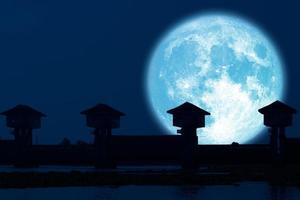 riflesso luna piena blu e diga silhouette nel cielo notturno scuro foto