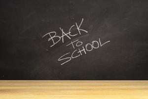 lavagna con frase scritta a mano di ritorno a scuola e tavolo in legno foto