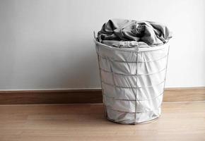cesto moderno con panni sporchi sul pavimento foto