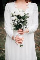 bouquet da sposa di fiori di rosa nelle mani della sposa foto