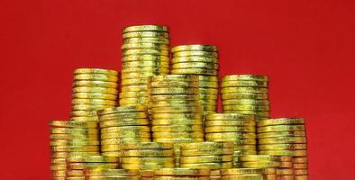 mucchio monete d'oro su sfondo rosso foto