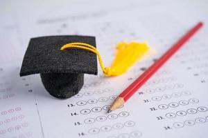 graduazione cappello e matita sul foglio delle risposte foto