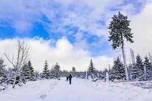 escursionisti nel paesaggio invernale nelle montagne brocken, harz, germania foto