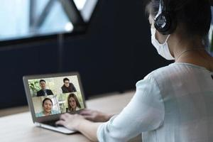 videochiamata asiatica della donna d'affari con i colleghi da casa foto