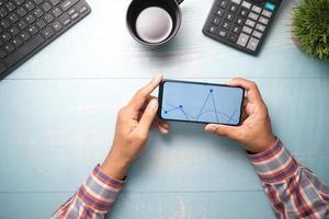 giovane che analizza il grafico azionario sullo smartphone foto