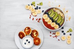 mousse di frutta in ciotole per con frutti di bosco e frutta su sfondo bianco foto