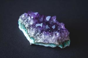 cristalli di drusa di pietra ametista su sfondo nero foto