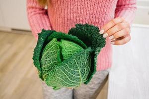 mani femminili che tengono una testa di cavolo verde foto