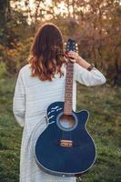 vista posteriore della giovane donna che tiene una chitarra nel parco al tramonto foto