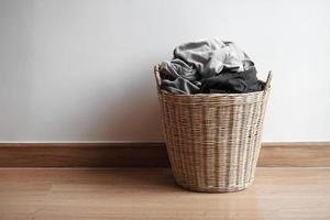 cesto di legno con panni sporchi sul pavimento foto