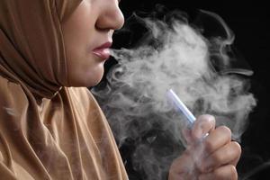Close up giovane donna musulmana che fuma sigaretta elettronica su sfondo nero foto