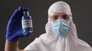 scienziato in una tuta protettiva mostra un vaccino sviluppato contro il covid. concetto di fine positiva della pandemia globale. foto