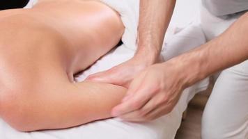 terapia di massaggio relax e concetto di trattamento per la cura del corpo. donna sdraiata sul letto con un asciugamano con massaggiatore che massaggia il relax delle mani nel salone della stazione termale. foto