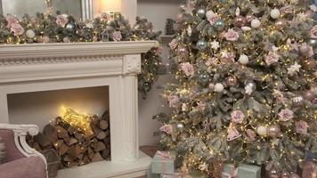camera accogliente con un'atmosfera natalizia. caminetto acceso, albero di Natale incandescente. ambiente domestico confortevole con candele. spirito di natale e capodanno. natale. sfondo video in loop. foto