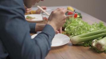 un uomo che mangia un'insalata vegetariana di verdure fresche. alimentazione sportiva e alimentazione sana foto