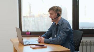 l'uomo indossa cuffie wireless effettuando videoconferenze chiamate di lavoro sul laptop parlando comunicando tramite webcam, manager insegnante maschio parlando fare chat online sul computer sedersi alla scrivania dell'ufficio di casa foto