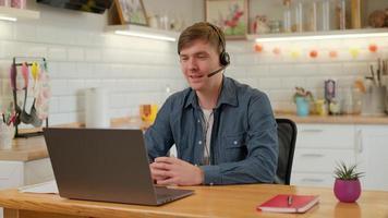 l'uomo d'affari sorridente indossa le cuffie wireless per effettuare una videochiamata in conferenza sul laptop. agente di call center professionista maschio, manager delle risorse umane che ha colloquio di lavoro con chat via webcam a distanza sul computer foto