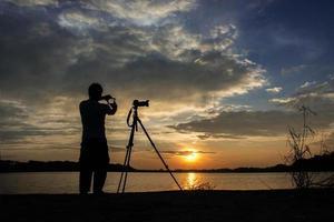 sagoma del fotografo con la sua composizione di controllo della mano al tramonto. foto