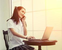 la donna della scuola usa il laptop per studiare e parlare al telefono seduto foto