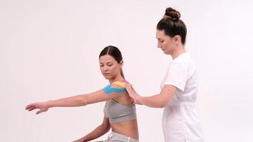 il terapista sta applicando il nastro kinesio al corpo femminile. concetti di fisioterapia e kinesiologia. foto